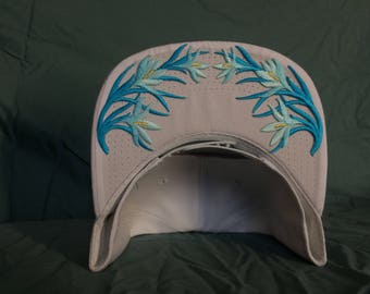 White snap-back cap with baby blue flower crown