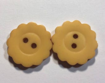 Two vintage scalloped cream bakelite buttons