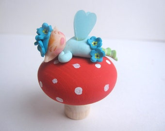 Figurine of miniature  forget me not Fairy on a toadstool