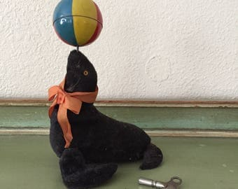 antique wind up seal circus toy with ball and ribbon