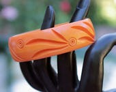Orange Bakelite Bangle Carved with Stylized Floral Design