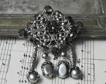 Vintage filigree brooch with black glass rhinestones.
