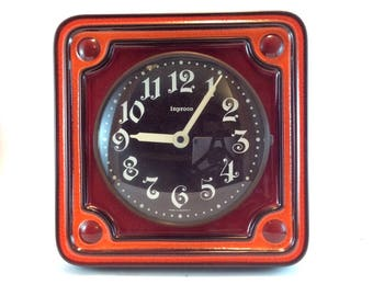 Inproco space age ceramic wall clock in orange, brown and reddish-brown. West-German art pottery wall clock. Seventies kitchen clock.