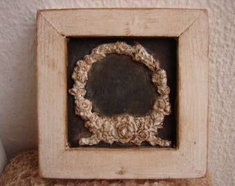 small,shabby roses wreath in grungy, old, white frame on charcoal painted background