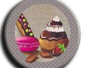 Aimant, Magnet rond de gourmandises avec 1 macaron, une religieuse, des chocolats, un éclair et une fraise au chocolat sur