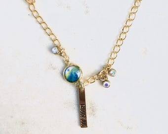 Choose Joy watercolor charm necklace, gold chain with blue tones painting and clear crystals, black words on gold.