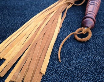 Brown split suede leather flogger featuring a beautiful turned ash wood handle
