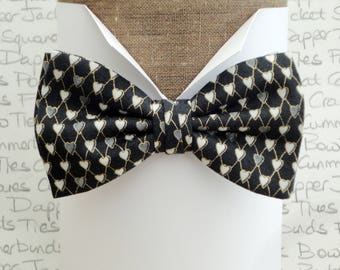 Bow ties for men, hearts edged in gold on a nearly black background