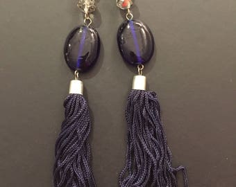 Long tassel silver necklace with blue beads.