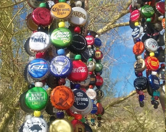 Rustic wind chime showcasing bottle caps with glass beads and a bottle opener down the center, recycling at its best!