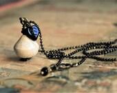 """Collier """"le pendule de Johanna"""" avec perle en céramique Raku blanc ivoire, mini feuille en verre noir et chaînette fine noir et bronze"""