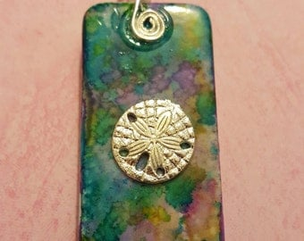 Multicolored domino with silver sand dollar charm
