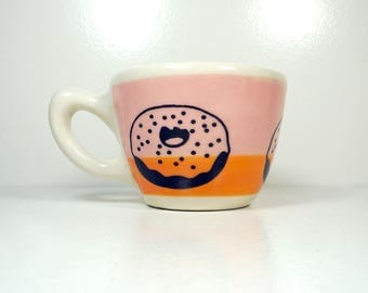 a 12oz cup painted in a color block of pink & orange with Donut prints READY TO SHIP