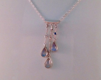 I call this pendant Rain. It has 3 labradorite pear sharped cabs and 1 blue and 1 white diamond on a cable chain.