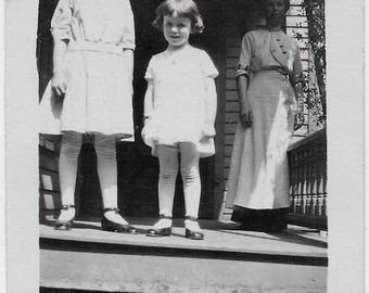 Old Photo 2 Girls wearing Dresses Hair Bow Woman in Background Long Dress on Porch 1910s Photograph Snapshot vintage