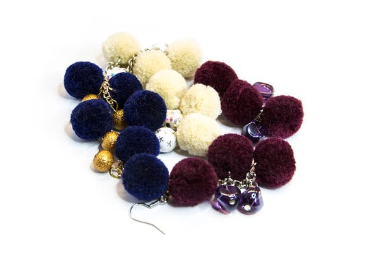 Dangle chain earrings with statement pom poms and beaded details