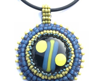 Blue, yellow-green and black fused-glass beaded bezel