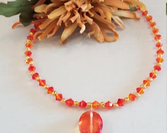 Orangey red Swarovski crystal necklace with gold spacer beads and crystal pendant