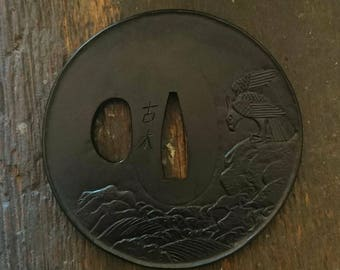 Tsuba, eagle on craggy rocks, breaking waves