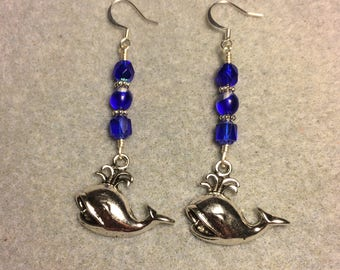 Silver spouting whale charm dangle earrings adorned with dark blue Czech glass beads.