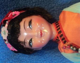 Oriental plastic doll 10 inches tall dressed in silk with ribbon braid trim