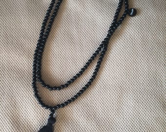 Man with black tassel necklace
