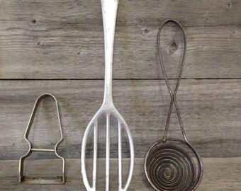 Vintage kitchen utensils: primitive beater, egg separator and vegetable peeler