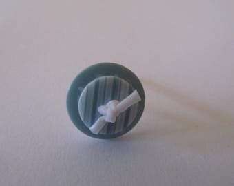 Ring with white plastic ring button