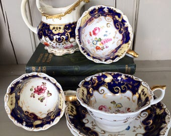 A Part Set of Antique Blue, Gold and Flowery Cups and Saucers