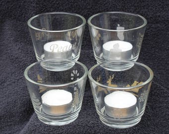 four tea light holders in a set with various christmas type images onto
