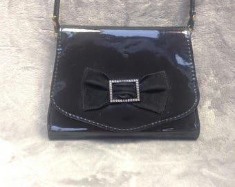 Black patent handbag with diamante bow detail and shoulder strap.  Made in England circa 1970s.
