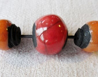 set of 3 round beads orange or red on black ground