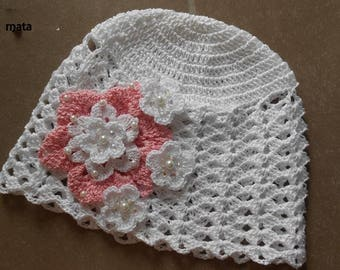 White baby bonnet crochet with a flower blanche.perles.