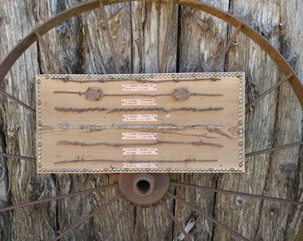 """6 pieces of 18"""" collectible antique barbed wire. Displayed on a 11 1/2 x 24 1/2 Barn d wood board and edged with tacks all around the board."""