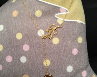 Golden necklace with a leaf and bird