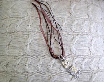 Silver colored chain and a Brown organza cord
