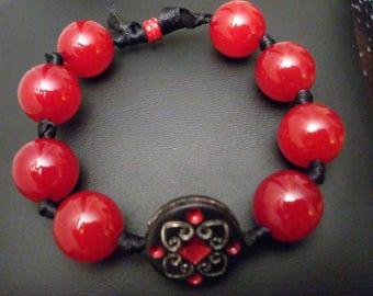 Bracelet red beads knotted on black satin ribbon