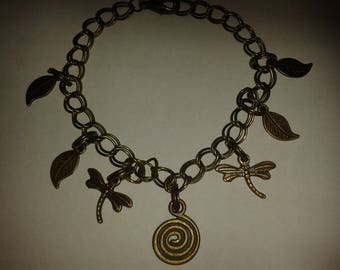 """Dragonfly"" with multiple charms, bronze bracelet."
