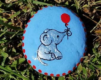 Cute elephant calf holding a balloon in his trunk painted rock