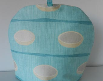Quilted tea cosy / cozy in retro style turquoise blue fabric with cream oval discs.  32 cm by 28 cm with cosy 7 ounce wadding