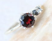 Round faceted garnet ring in silver bezel and prongs setting and white sapphire on the side with sterling silver high polish finished band