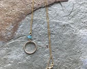 Fine gold chain with apatite accents and a gold ring pendant