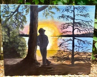 Lakeside quiet morning sun rising over water young man leaning against tree taking in the view of sun glistening on lake