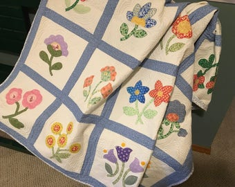 Quilt with blocks of appliqued flowers