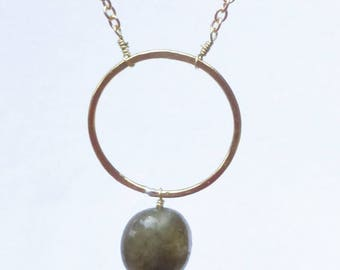Hammered brass circle pendant with green gemstone