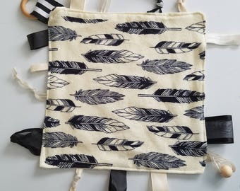 """Teething Chew Tag Blanket for baby. Ivory with black feathers, ribbon, bead, wood ring pendant. 10""""x 0"""" handmade by Everyday Gourmet"""