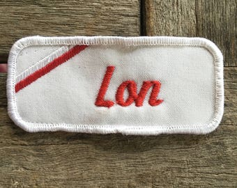 "Lon. A white work shirt name patch that says ""Lon"" in red script with white border"