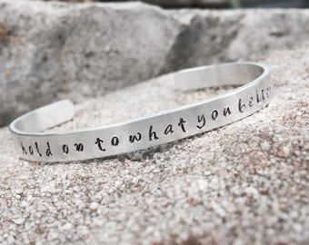 "Mumford & Sons hand stamped aluminum bracelet with lyrics ""hold on to what you believe"""