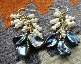 Draped Pearl Earrings are stacks of white rice pearls on gold, dangling above trios of gleaming Peacock Keishi pearls. Pearls for days!