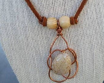 copper wire wrap with an acrylic stone look bead on a leather cord with wood bead accents